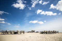 Sandy beach St. Peter-Ording. Sandy beach with beach chairs and buildings in St. Peter-Ording at the North Sea in Germany on a sunny day in spring Stock Photography