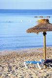 Sandy Beach With Straw Umbrellas et lits pliants Photos stock