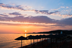 Sandy beach with stray sunshades and orange chairs at sunset in Sithonia. Greece Stock Photography