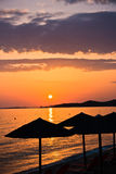 Sandy beach with stray sunshades and orange chairs at sunset in Sithonia. Greece Stock Photos