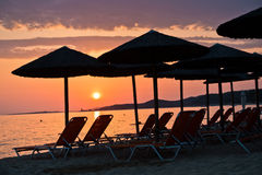 Sandy beach with stray sunshades and orange chairs at sunset in Sithonia. Greece Stock Photo