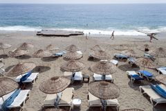 Sandy beach with sun loungers and straw umbrellas on the Turkish sea coast, Mediterranean sea. Turkey royalty free stock photos