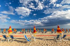 Sandy beach with sun loungers and umbrellas. Sandy beach with sun loungers and umbrellas in Italy, Europe Royalty Free Stock Images