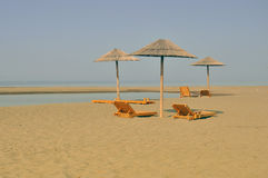 Sandy beach with sunbeds. Sandy,lonely beach,with umbrellas and sunbeds Royalty Free Stock Photo