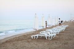 Sandy beach sunbeds Stock Images
