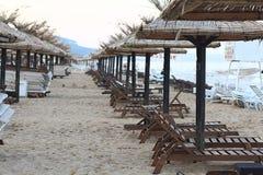 Sandy beach sunbeds umbrellas sea Stock Image