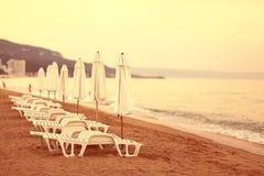 Sandy beach sunbeds umbrellas sea Stock Images