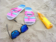 Sandy beach with sunglasses, flip-flops and suncare milk Royalty Free Stock Photos