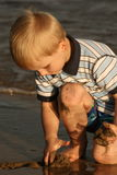 Sandy beach in the sunset. Small boy catching the last minutes of a day Royalty Free Stock Photos
