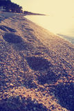 Sandy beach at sunset with footprints on the sand; faded, retro style Stock Photography