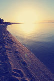 Sandy beach at sunset with footprints on the sand; faded, retro style stock photo