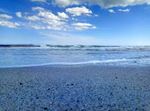Sea surf sky sand sand beach. Sandy beach surf of the sea wave and the blue sky and a few clouds Stock Images
