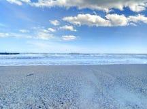 Sea surf sky sand sand beach. Sandy beach surf of the sea wave and the blue sky and a few clouds. Surf of the sea to a sandy beach Stock Photos