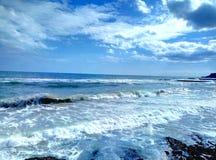 Sea surf sky sand sand beach. Sandy beach surf of the sea wave and the blue sky and a few clouds. Surf of the sea to a sandy beach Stock Image