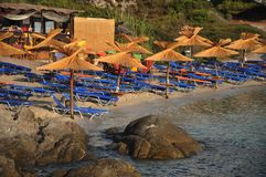 Sandy beach with thatched parasols and deck chairs. Beach bar Royalty Free Stock Photography