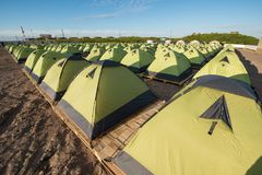 A number of green tourist double tents in line royalty free stock images