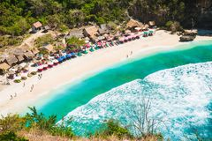 Sandy beach with turquoise ocean and bright colorful umbrellas, Nusa Penida. Sandy beach with turquoise ocean and bright colorful umbrellas royalty free stock photography