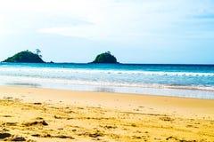 Sandy beach, waves, blue turquoise sea hills and blue sky sea horizon Stock Photo