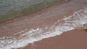 Sandy beach and waves, close-up. Texture of sand and water. Pict stock video footage