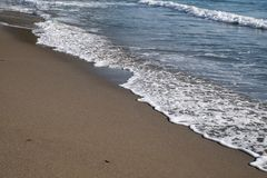Sandy beach and waves. In summer stock images