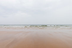 Sandy beach and wavy sea surface on the wales coast on a cloudy Royalty Free Stock Photography