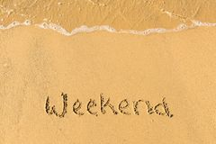 Weekend written on sand. Sandy beach with Weekend sign scribbled on beach sand. leisure time concept stock images