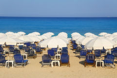 Sandy beach with white parasols and sunbeds Royalty Free Stock Photo