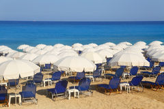 Sandy beach with white parasols and sunbeds Royalty Free Stock Images