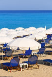 Sandy beach with white parasols and sunbeds Stock Images