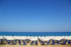 Sandy beach with white parasols and sunbeds Stock Photos