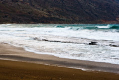 Sandy beach with white surf. Formed as the incoming waves break over the shallow rocks in a marine bay royalty free stock photos