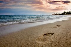 Free Sandy Beach With Footprints In Sand, Blue Wavy Sea And Cloudy Sky In The Dusk Stock Images - 138865034