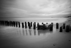 Sandy beach with a wooden breakwater Royalty Free Stock Images