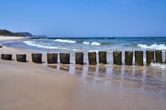 Sandy beach and wooden breakwaters. On the Baltic coast royalty free stock photos