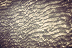 Sandy bottom with reflecting sunlight from water ripples Royalty Free Stock Photo