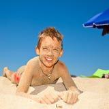 Sandy boy on a beach Stock Photos