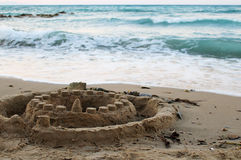 Sandy castle on beach at the sea. Photo of sandy castle on beach at the sea stock photo