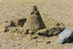 Sandy castle built by children with wet sand on the beach. Castles on the sand. Fun in the sand on the beach on a sunny day. Concept of summer vacation and stock image