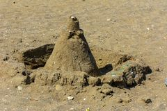 Sandy castle built by children with wet sand on the beach. Castles on the sand. Fun in the sand on the beach on a sunny day. Concept of summer vacation and stock photos