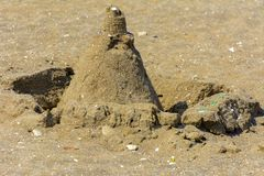 Sandy castle built by children with wet sand on the beach. Castles on the sand. Fun in the sand on the beach on a sunny day. Concept of summer vacation and stock photography