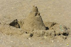 Sandy castle built by children with wet sand on the beach. Castles on the sand. Fun in the sand on the beach on a sunny day. Concept of summer vacation and stock photo