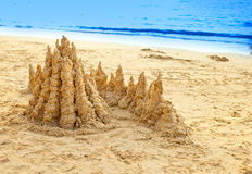 Sandy castle at the sea edge Stock Image