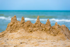 Sandy castle at the sea edge Royalty Free Stock Photos