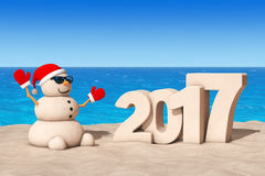 Sandy Christmas Snowman at Sunny Beach with 2017 Ney Year Sign. Royalty Free Stock Images