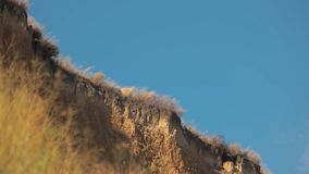 Sandy cliff and sky. High dry grass. Become one with nature. Search for inspiration stock video
