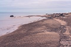 Along the beach are larger and smaller stones. The sandy coast and horizon of the Baltic Sea; the sea is calm, without waves; along the beach are larger and stock images