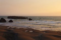 Sandy coast of the Pacific Ocean during sunset, sunrise royalty free stock photography