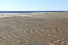 Sandy coastal strip with sharply outlined shade. S from roughnesses of sand Stock Photography