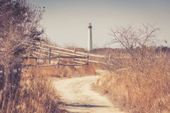 Sandy curved walking path leading to lighthouse Stock Image