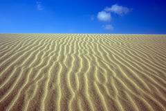 Sandy desert. Sandy dunes in desert and cloudy sky royalty free stock image